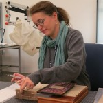 Photo of Louise Crean working on restoring a book