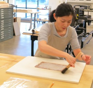 Instructor Minah Song Brushing a Single Sided Lined Object onto a Drying Board