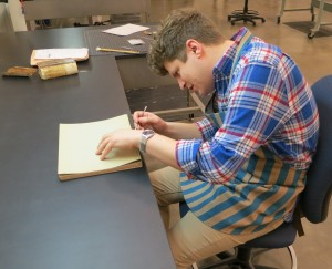 William Bennett, at work cleaning the spine of a book.