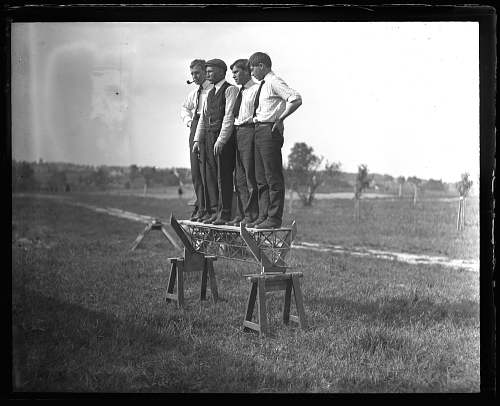 One-half left front view of four unidentified men standing on  a tetrahedral beam supported on sawhorses; part of Alexander Graham Bell's tetrahedral kite experiments of 1907.