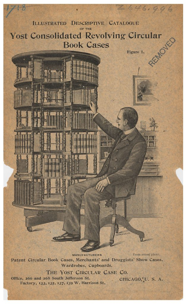 man sitting in chair pulling a book from a revolving bookcase