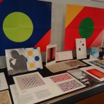 Two versions of Paul Reed posters behind colorful ephemera related to Reed, Thomas Downing, Howard Mehring and others.