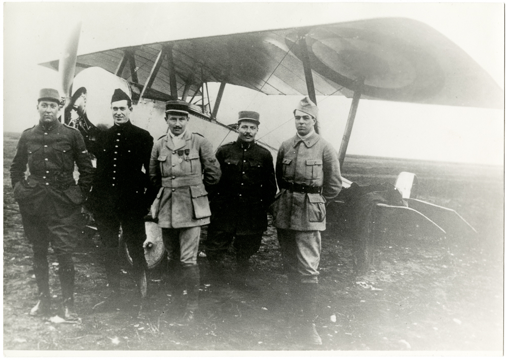 Informal group photograph of early Lafayette Escadrille members (left to right) James McConnell, Kiffin Yates Rockwell, Captain Georges Thenault, Norman Prince, and Victor Chapman; all posed in front of a Nieuport XI at Luxeuil, France, 1916.