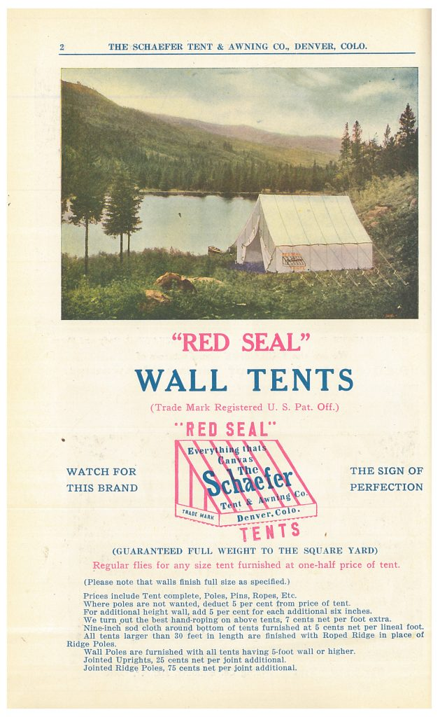 """Red Seal"" Wall Tent set up at a campsite near a lake"