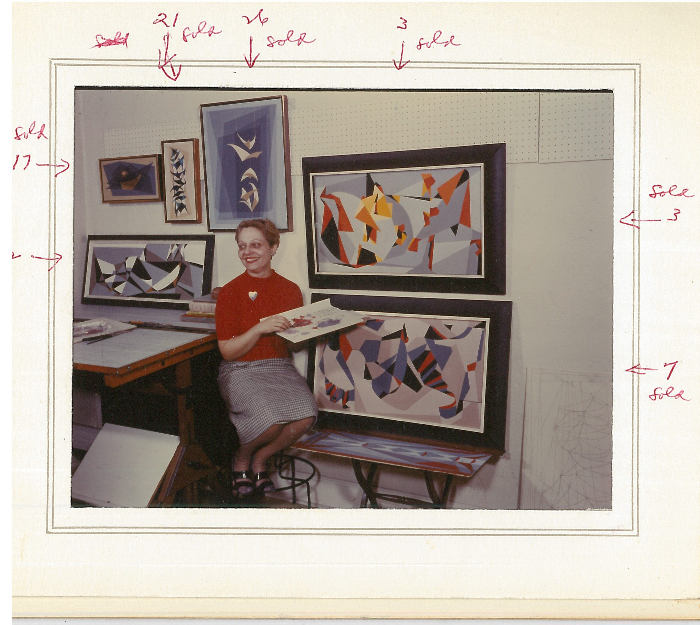 Color photo of Mae Jurow posing in front of several of her art works.