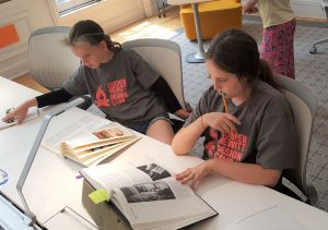 This image features 2 young girl Design campers sitting looking at library works.at table looking