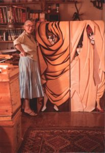 Image of Whitney Kent standing in front of one of her wooden sculpture pieces.