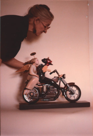 Photo of Whitney Kent adjusting one of her sculptures.