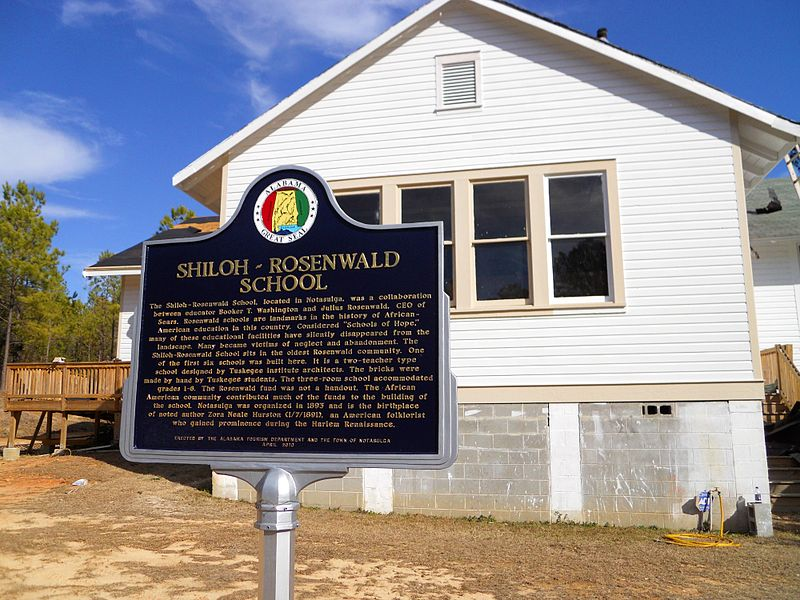 Exterior of Rosenwald School in Notasulga, Alabama. White building with historic marker in front.