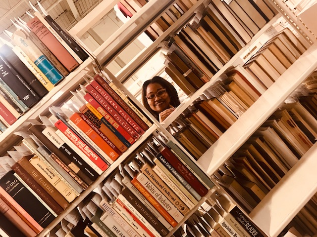 Intern Angela Brooks peering through space in book shelves.