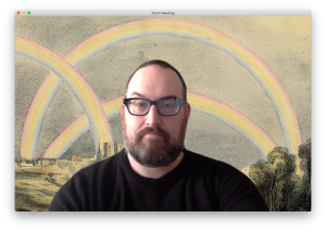 Screenshot of man in foreground with digital background of rainbows.