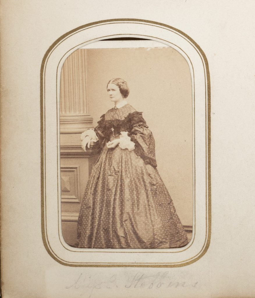 Carte de VIsite of Emma Stebbins. 19th century photography of Caucasian women standing in dark hoop skirt dress.