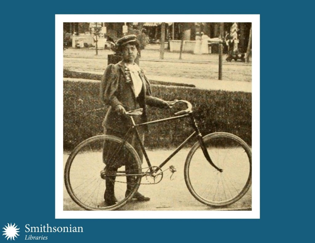 19th century photograph of young woman and bicycle.