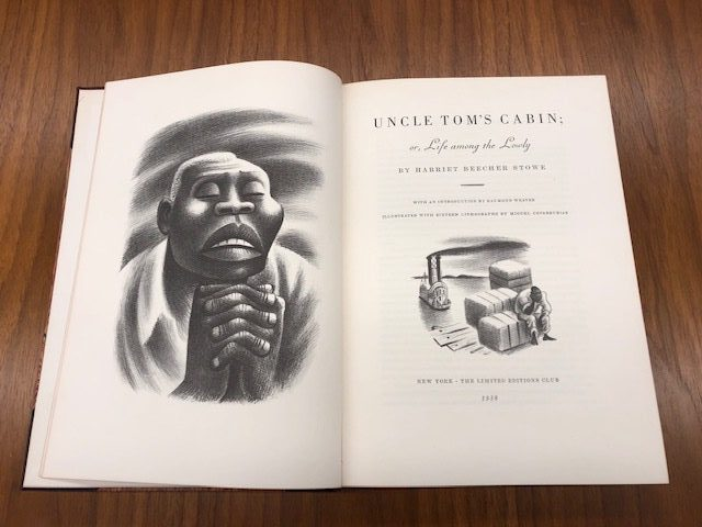 Photo of book, open on table. Left page has illustration of enslaved man.
