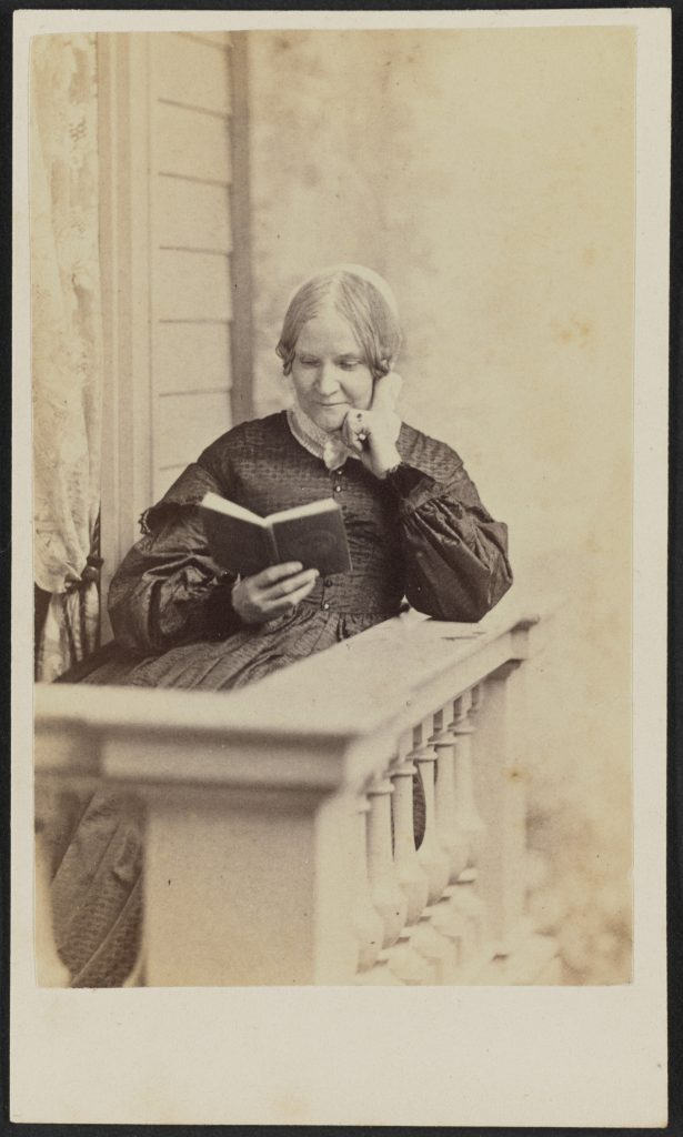 Carte-de-visite of Lydia Maria Child shown in half portrait. Child is seated behind the corner of a white columned banister, possibly on a balcony outside a house with wooden siding next to a window with a lace curtain. Her left elbow is propped on the railing and her left hand rests on her chin. She holds a book in her right hand, which she is reading. Her hair is parted at the center and gathered into curls or braided above her ears, then pulled behind her head. She wears a dark colored bodice and skirt with dropped bell sleeves and white lace collar. There is a ring with a dark stone on her left hand ring finger.