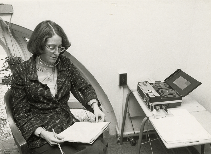 Pam Henson is seated at a desk. She is wearing headphones attached to an audio recording machine from the 1970s.