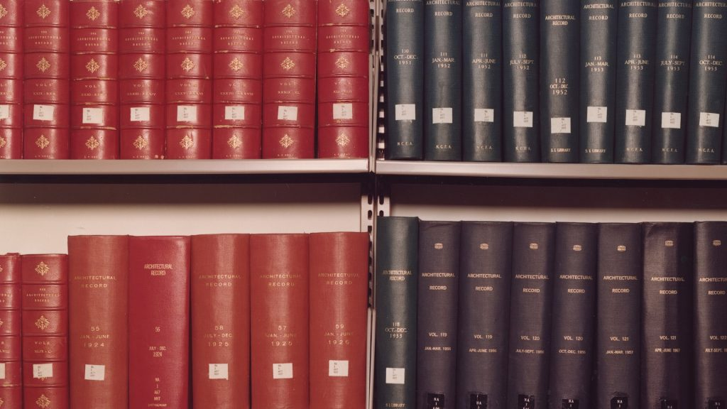 Color photograph of book spines on shelf, half red, half navy blue.