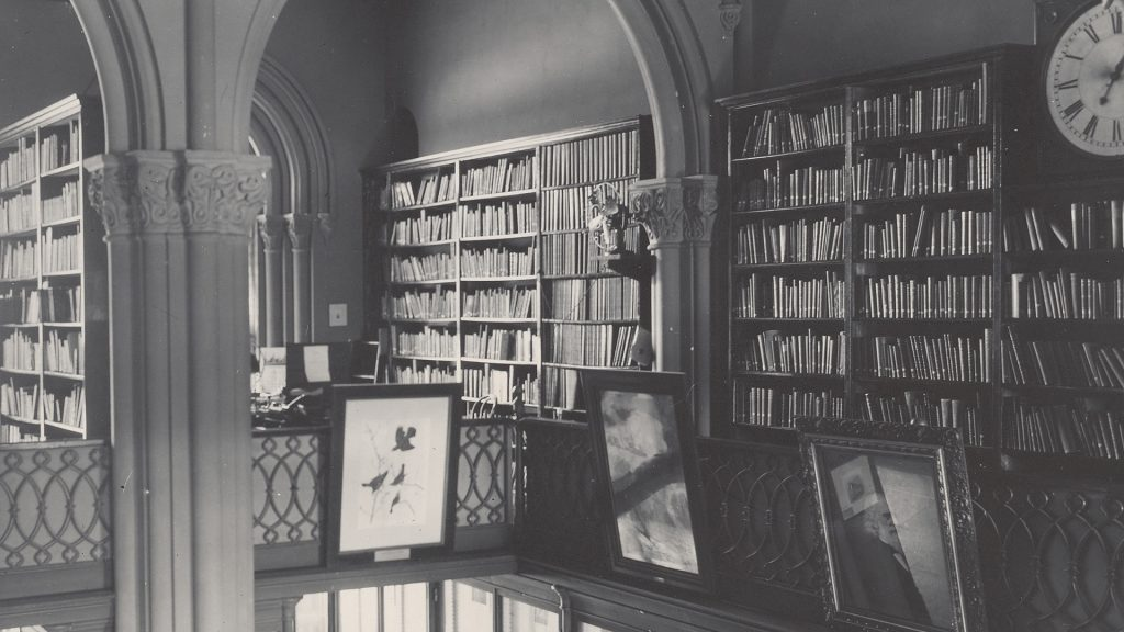 Black and white photograph of library with shelves of books and framed pictures.