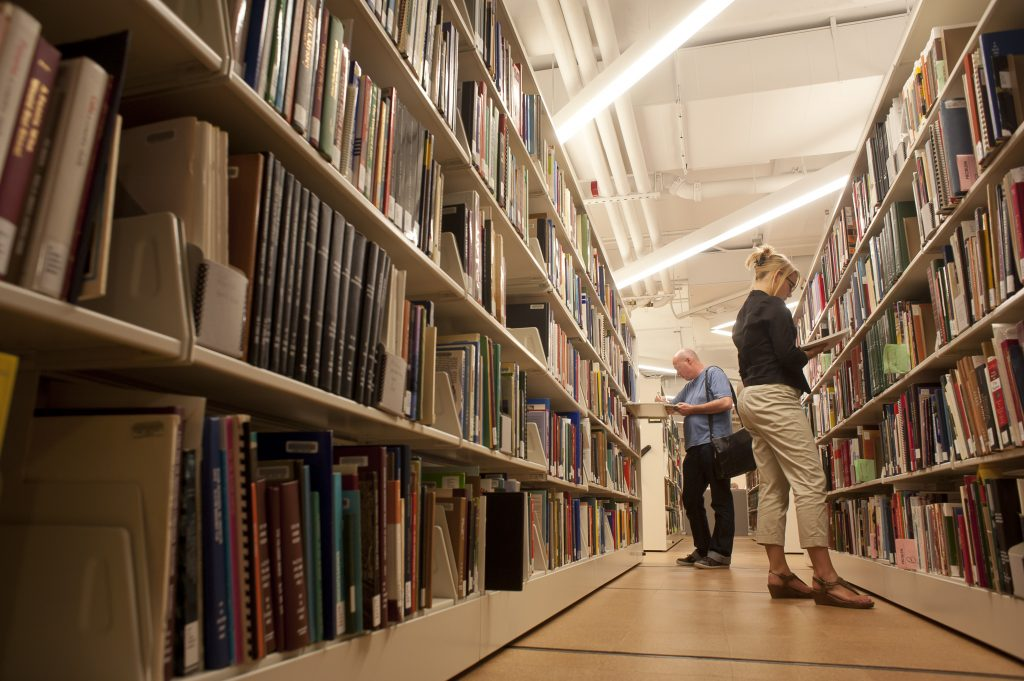 Photograph of two people looking at books on library shelves.