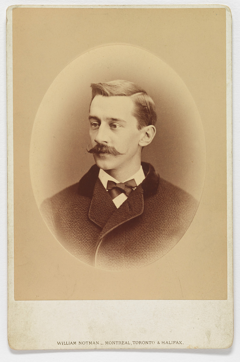 Late 1800s photograph of young man with moustache wearing a suit.
