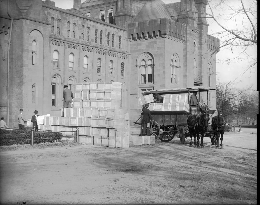 Black and white photograph of exterior of Smithsonian Institution Building. In front are men stacking dozens of large boxes. Boxes are also being packed on to a cart pulled by two horses.
