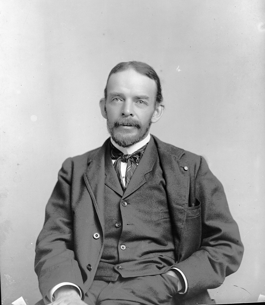Black and white photograph of man with beard and mustache. Man is seated, wearing a suit.